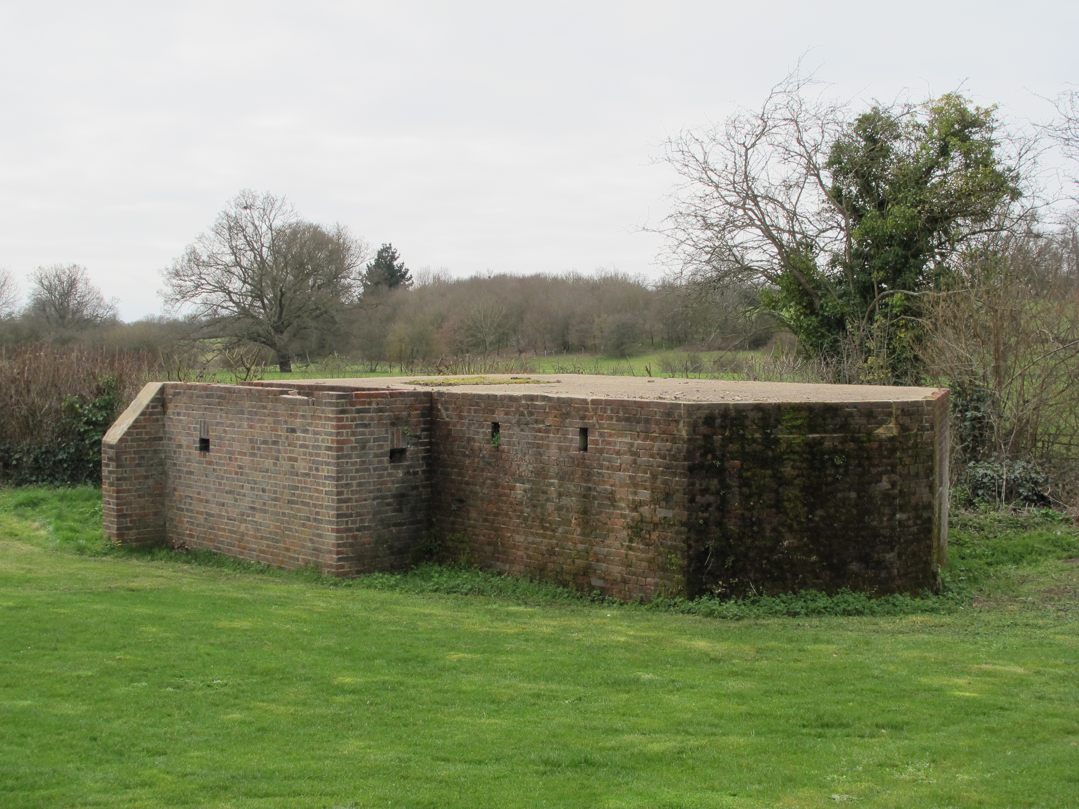 Rear view showing blastwall with two loopholes, note narrow vertical smoke/fume vents at top of the pillboxes rear wall