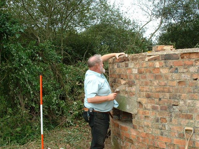 Penetration by ivy behind the top layer of bricks was found to have caused damage in some areas. Here John Hellis gets to grips with relaying some of the bricks and repointing other key areas.