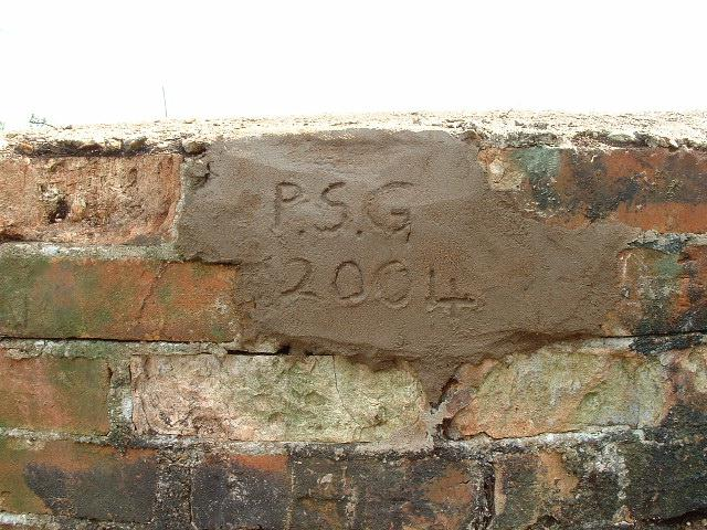 Stabilising part of the wall with mortar and adding our logo!