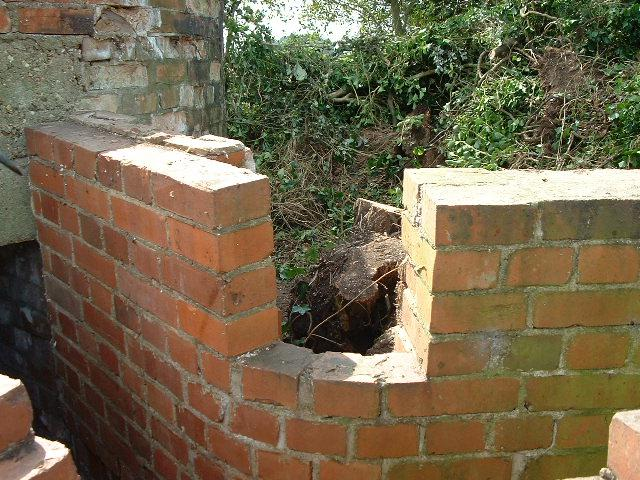 `Loophole` in entrance wall. Note how the wall on the left hand side is leaning in due to the tree (now removed) forcing it over.