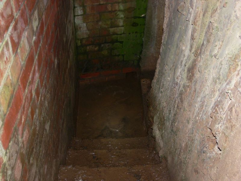 Bottom of main stairs, drain hole to bottom of other stairway.