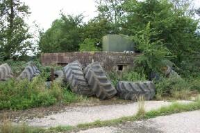 Front Elevation showing tractor tyres and an old oil tank acting as 'camouflage'.
