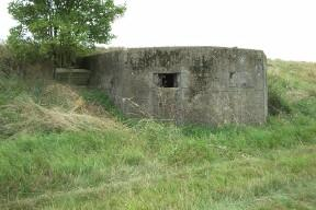 Elongated Concrete Pillbox runs through the Sea wall. Porch and entrance on the landward side with a Cruciform Internal Wall.