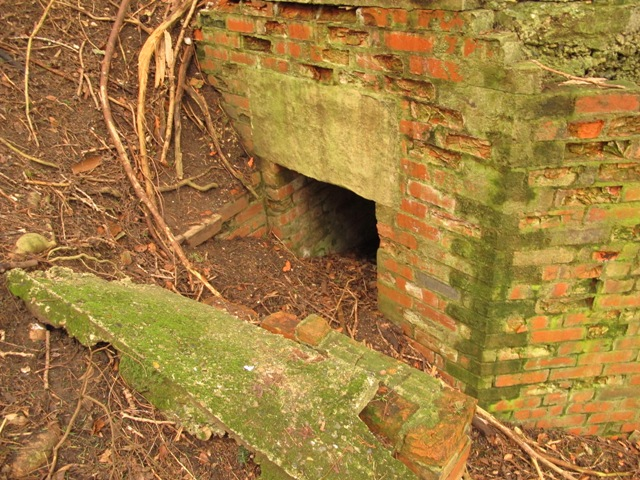 Dug in entrance protected by brick side wall.