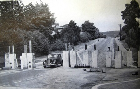 A typical Roadblock showing large concrete obstacles with RSJ uprights and Barbed Wire. Note oil lamps for illumination after dark. Picture most probably taken in Southern England, From wartime publication, photographer unknown.