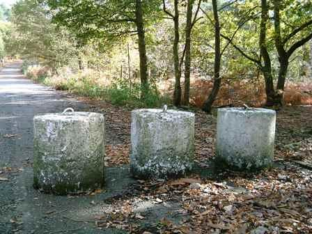 Three Concrete Cylinders with metal hoops still used for blocking a road today.