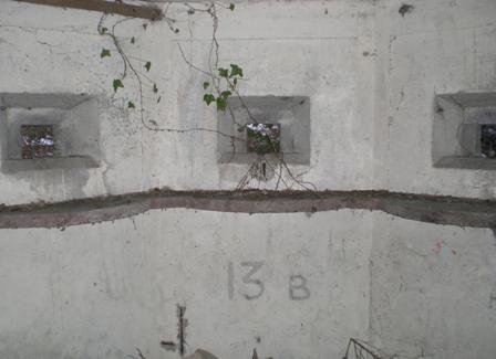 Number 13B painted upon the white washed inner wall.