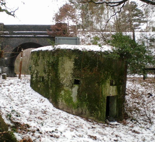 Eight sided bulletproof pillbox defending both Curzon Railway Bridge and Basingstoke Canal Bridge to Pirbright Barracks in Surrey.