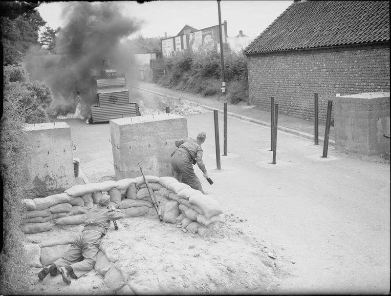 Members of the Home Guard stage an attack on an enemy 'tank' - in reality a corrugated iron mock-up - as they defend a concrete road barrier with petrol bombs, August 1940. THE HOME GUARD DURING THE SECOND WORLD WAR. © IWM (H 2722) IWM Non Commercial Licence