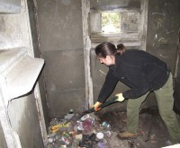 Sara scraping and shovelling the rubbish prior to bagging and removal.