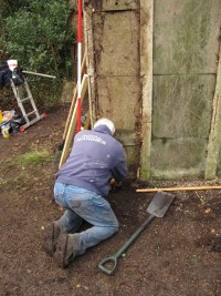 David working on removing embedded roots and ivy